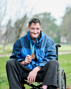 Murray sitting in his wheelchair, smiling with a bronze medal in his right hand.