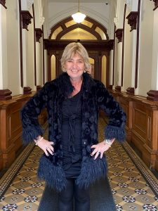Linda is standing in a corridor wearing a black feather coat and black dress.