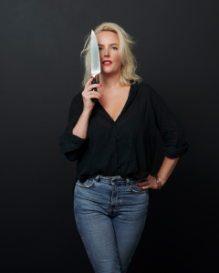 Lucy Tweed in front of a dark background, wearing jeans and a back shirt. She'd holding a chef's knife to her face.